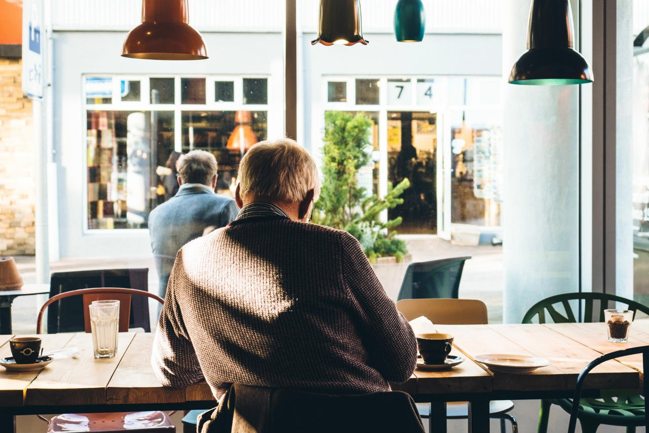 elderly man sitting at table in cafe