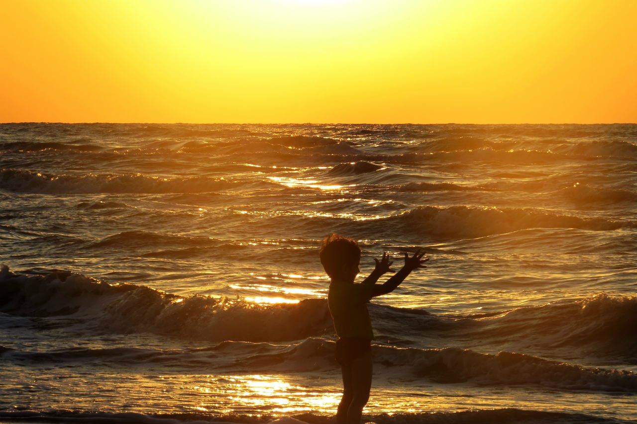 Child at beach with sunset