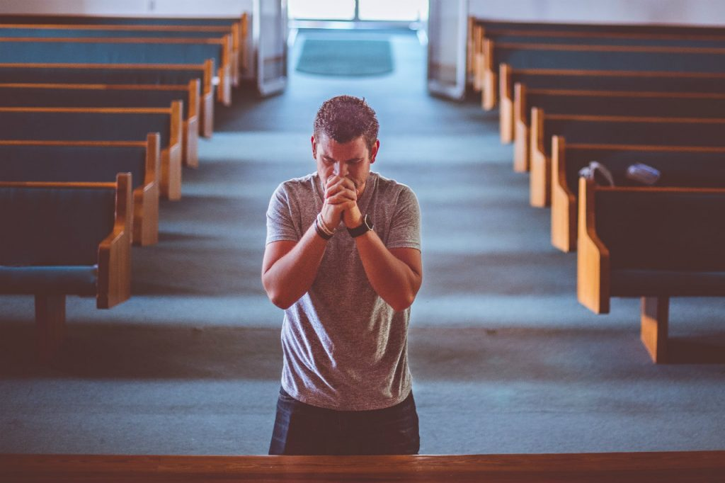 man on his knees praying