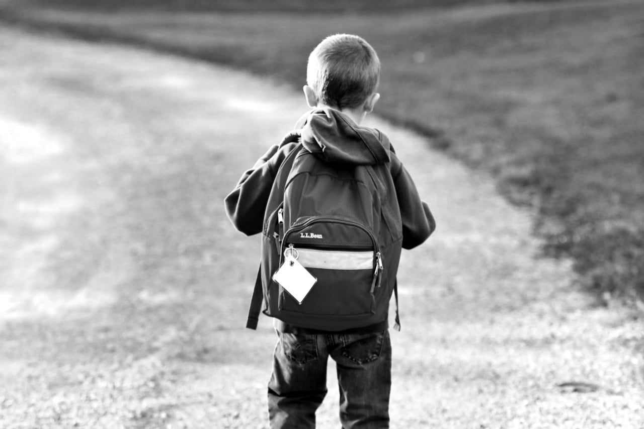 boy with backpack walking alone