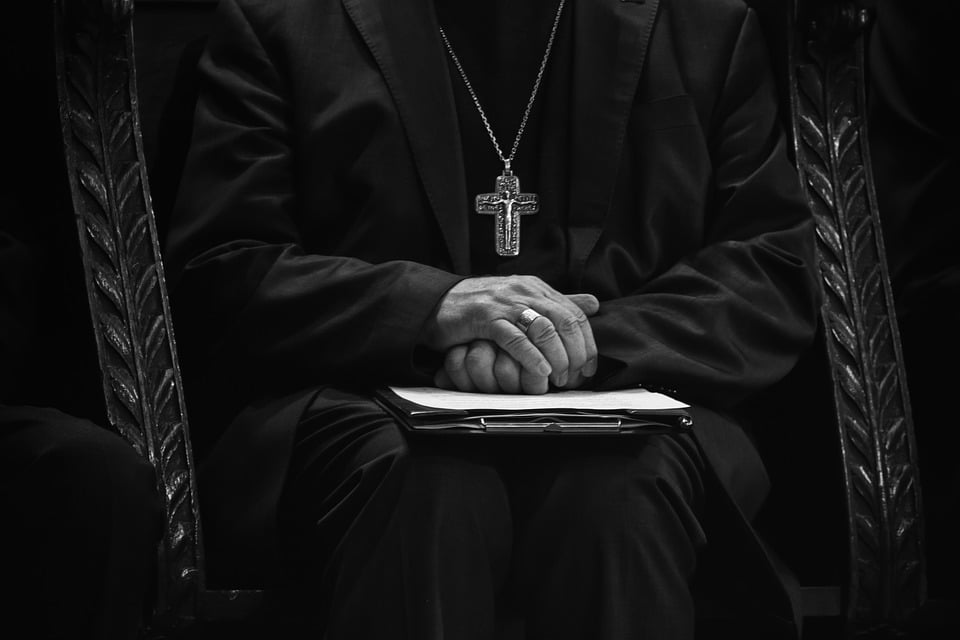 priest holding paperwork