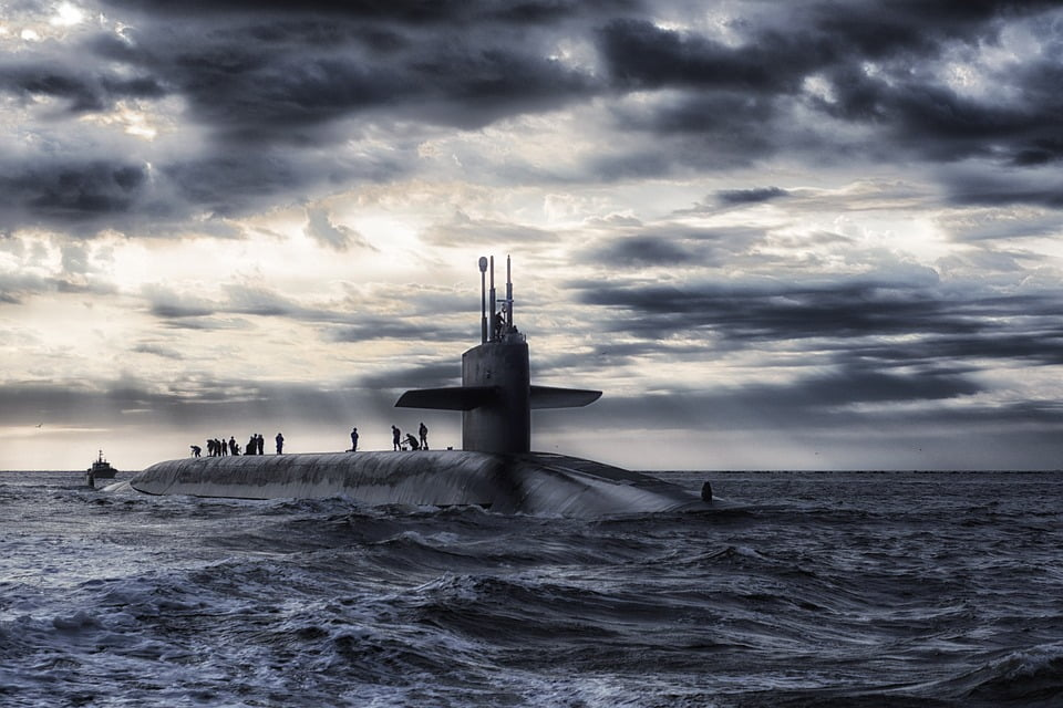 navy personnel on the top of a submarine at sea