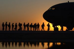 australian soldiers getting onto a plane at sunset