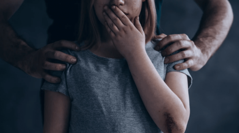 abused girl crying with perpetrator behind her