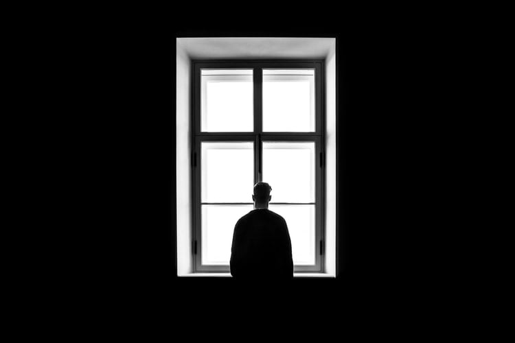 lonely man looking out window