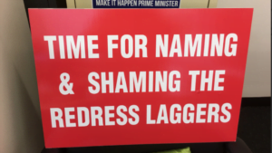 national redress scheme sign that says 'time for naming & shaming the redress laggers'